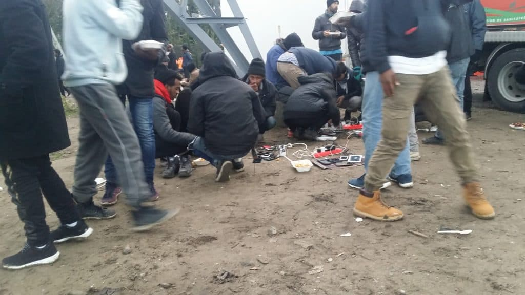 Migrantes cargando sus celulares en Calais